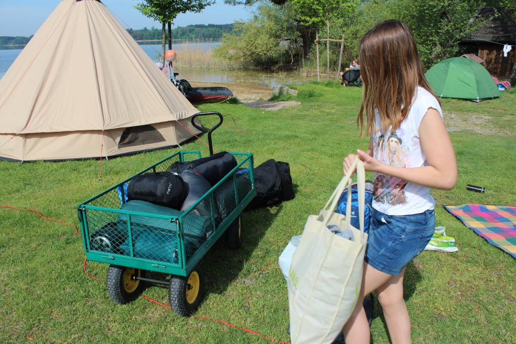 Zelten mit Kindern am See und mit Bollerwagen voller Camping-Ausstattung