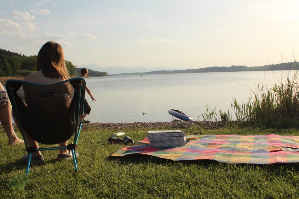 Am Strand vom Campingplatz: Kind auf Campingstuhl, Pizza auf Picknick-Decken