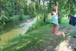 Springendes-Kind-vorm-Zelt-direkt-am-Flussufer